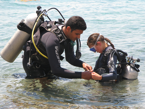 Dive instructor and girl scuba diving
